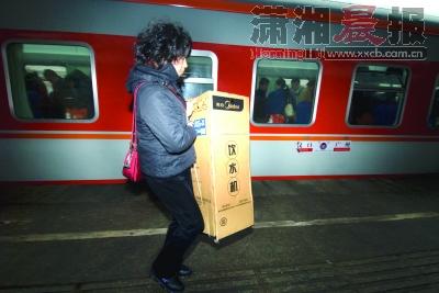 广州到汉口的列车停靠长沙,一位乘客搬着一台饮水机下车.