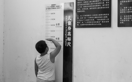 7月13日,长沙汽车南站过渡站,小朋友正用标尺测量身高.